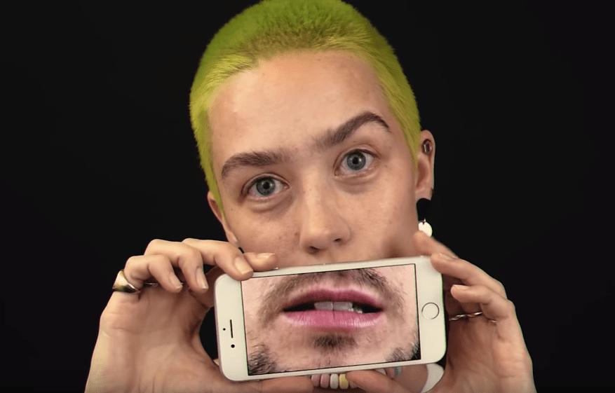 Девушка прикрывает рот смартфоном